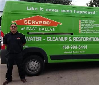 Male employee Jesus standing next to SERVPRO green truck